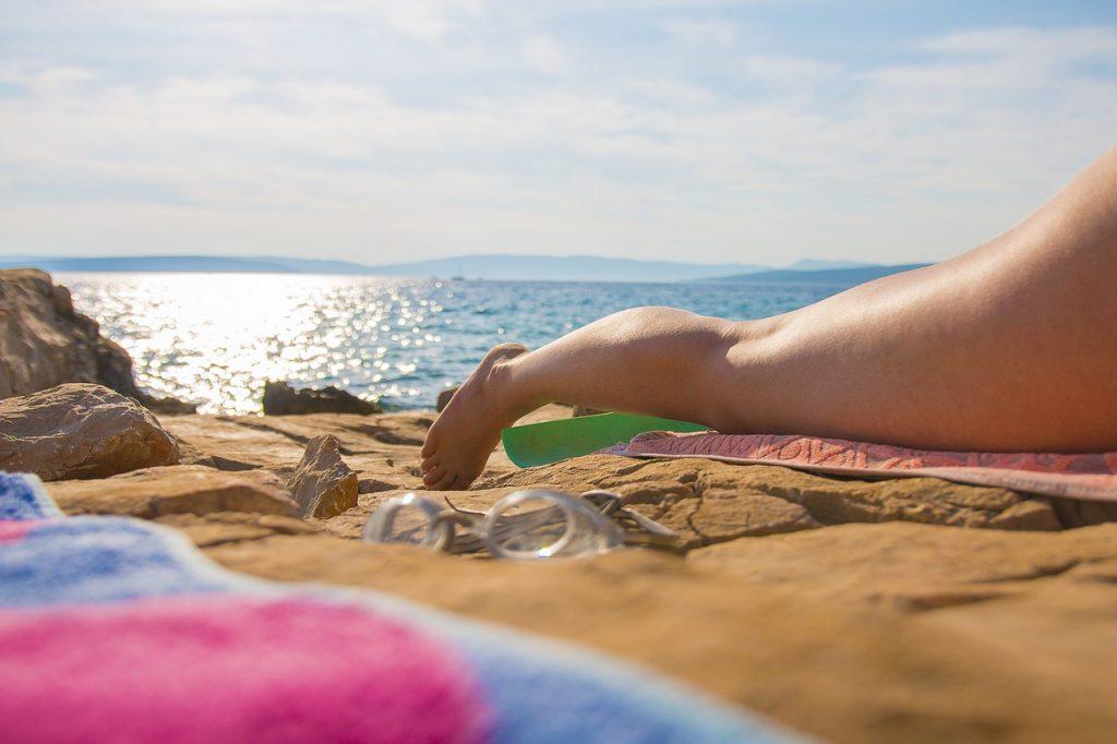 Pri mori leží žena, vidieť jej nohy