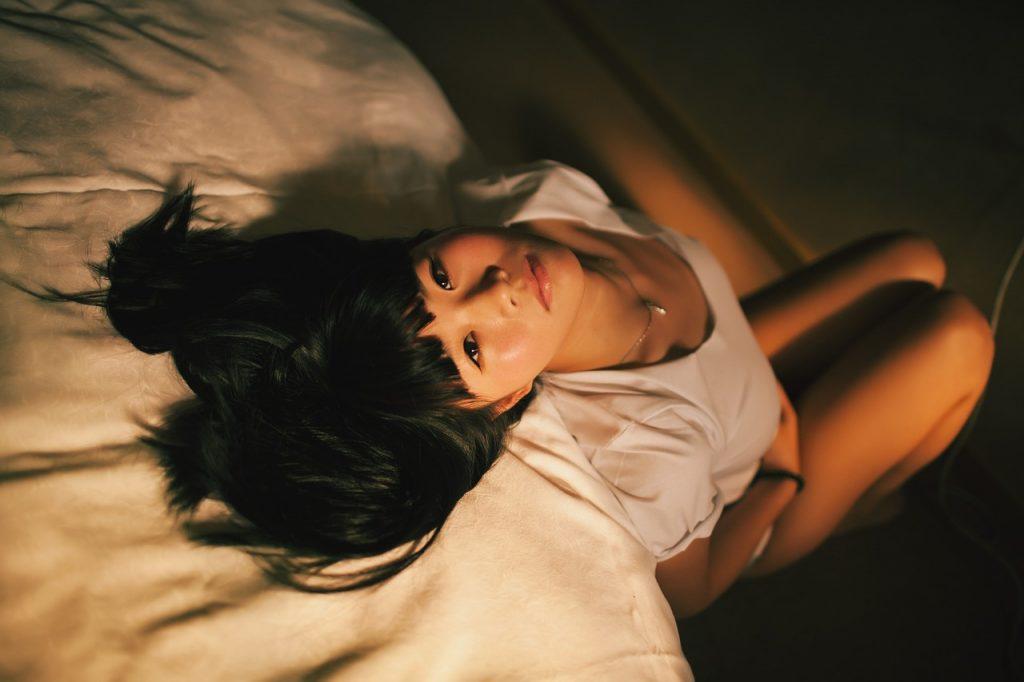 Žena sedí pri posteli, má bolesti spôsobené vaginálnou mykózou