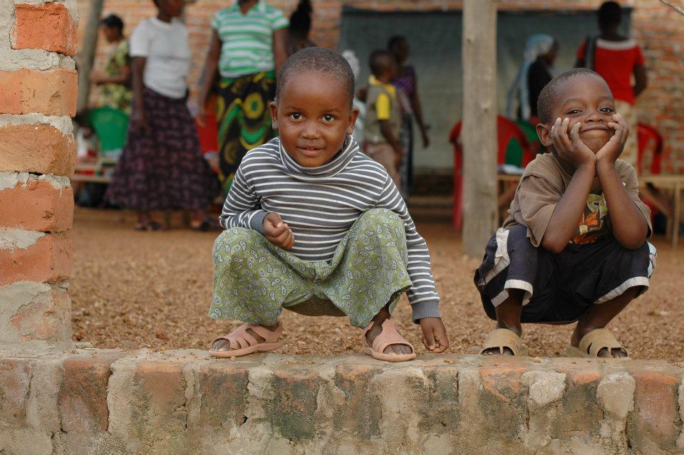 Dve deti z Afriky čupia a pózujú pred fotoaparátom