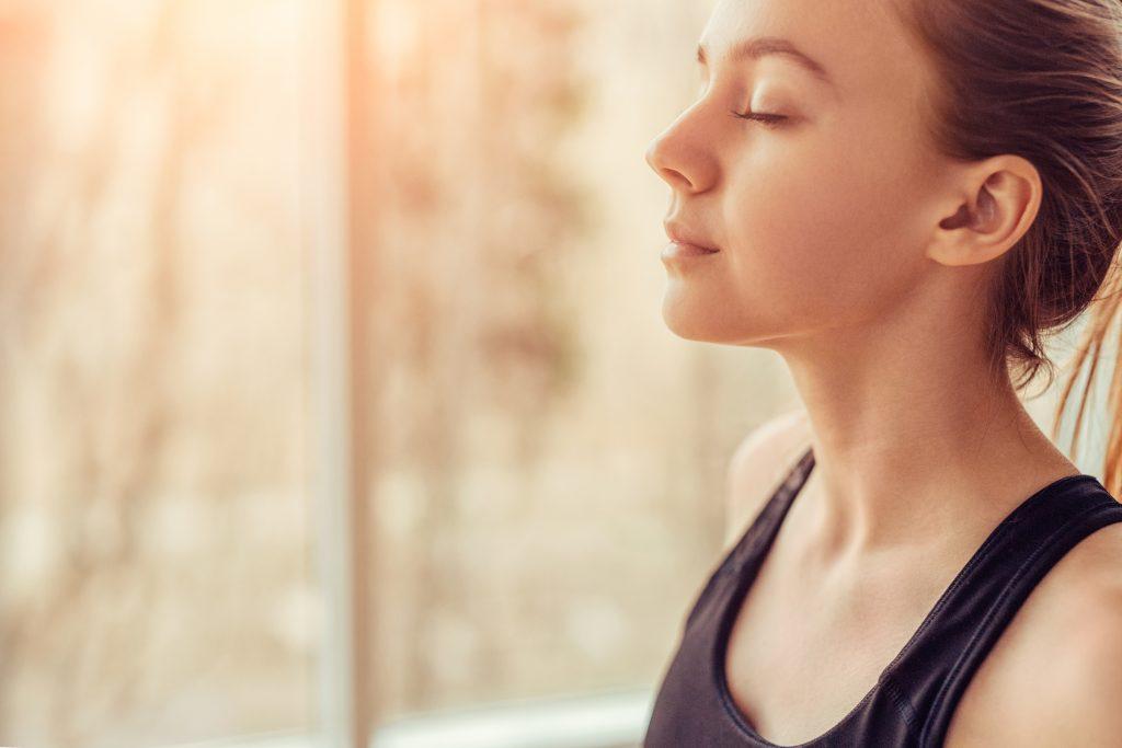 Žena má zatvorené oči, sústredí sa na správne dýchanie