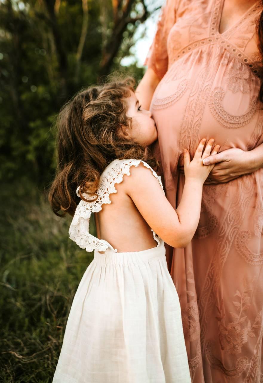 Dievčatko bozkáva brucho tehotnej mame