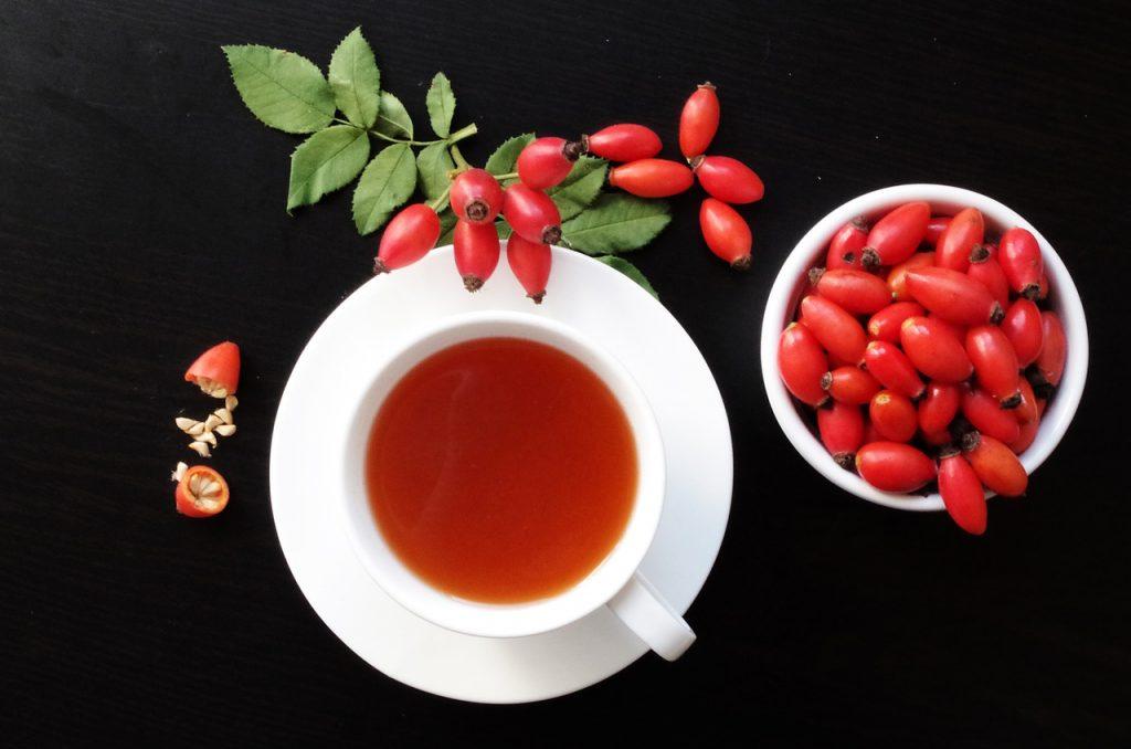 Šípkový čaj v bielej šálke a červené šípky v miske